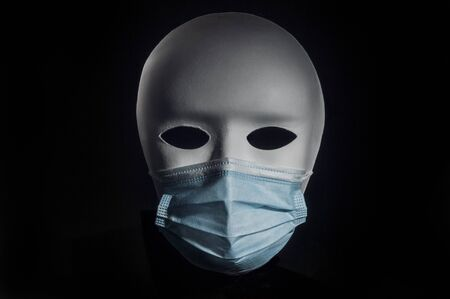 White theatrical mask wearing a surgical mask on black background