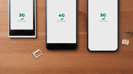 Mobile network evolution concept: comparison between 3g 4g and 5g smartphones on a wooden table Stockfoto