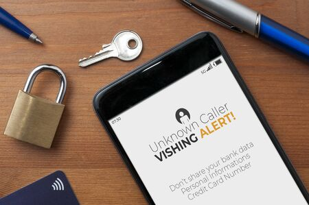 Vishing (voice phishing) concept, a smartphone on a table show an unknown caller call with vishing alert and a reminder to not share bank data, personal informations and credit card number
