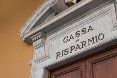 Carrara, Italy - June 14, 2020 - The metal sign of an italian savings bank on a big marble portal Redactioneel