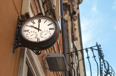 Old style street clock at 10 am in Italy