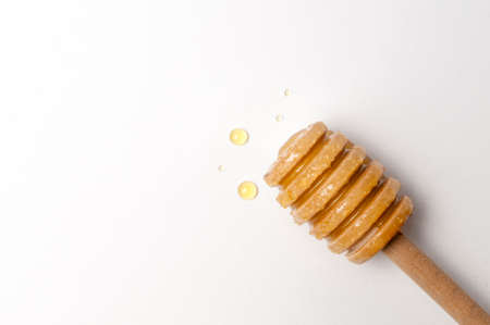 Honey dipper with some honey drops on white background