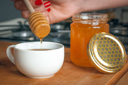 Woman pour honey into a cup of coffee as sweetener Stockfoto
