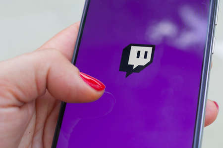 Carrara, Italy - July 6, 2020: Woman run Twitch application on a smartphone outdoor. Twitch is a live streaming platform owned by Amazon