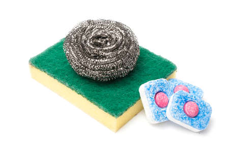 Dish washing items on white background: three dishwasher tabs and a wool cleaning pad over a sponge with scouring pad