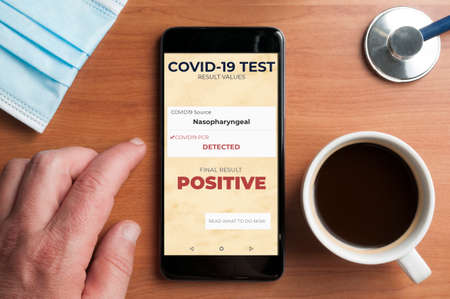 Man check the result of a positive covid-19 test on a smarthpone Stockfoto