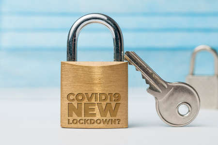 New lockdown due to covid-19 concept, a lock and a key with a surgical mask as background with the text: covid19 new lockdown. New outbreaks in the USA are likely to lead to a new closure. Stockfoto