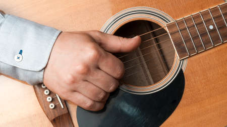 Close-up of a man in shirt playing fingerstyle guitar Stockfoto