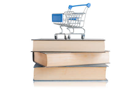 Shopping cart on top of a pile of books with reflection on white background