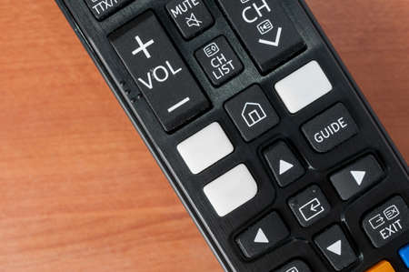 Tv remote control with white bank buttons for on demand services logos on a wooden table