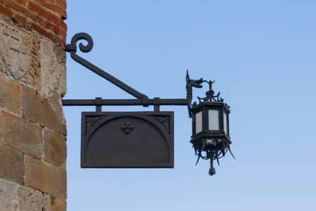 Blank old fashioned metal store sign with lantern hanging on the corner of a stone wall 스톡 콘텐츠