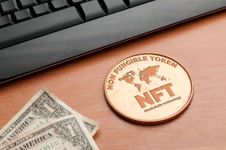 Nft (non fungible token) concept: big copper coin on a wooden table with a computer keyboard and two dollar bills