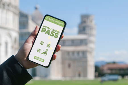 Digital Green Pass concept: Woman hold a smartphone in front of the Pisa leaning tower that show an hypotetical app for the Digital Green Passport (or digital pass certificate)