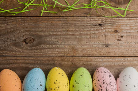 Simple easter background: colored easter eggs on a wooden table 스톡 콘텐츠