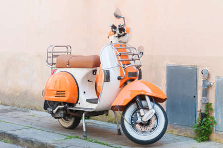 Pisa, Italy - March 25, 2021 - Vintage Vespa bike parked in an alley