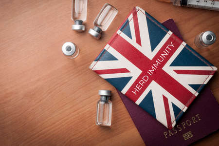 Herd Immunity concept: wallet with Uk flag over a passport along with some vaccine vials and a syringe on a wooden table