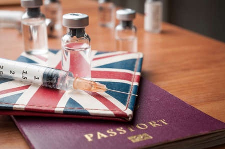 Uk vaccination concept: syringe and vaccine vial over a great britain flag wallet and a passport