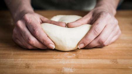 Woman kneads bread on wooden cutting board