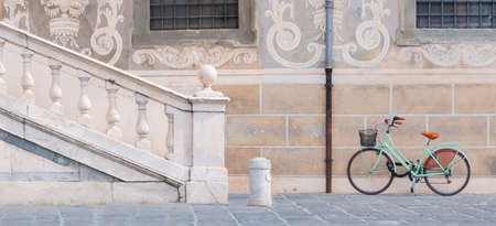 Bicycle parked next to the marble handrail of a historic building
