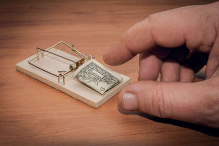 Man try to steal a one dollar bill banknote from a mouse trap