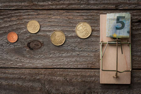 Path of coins leads to a banknote resting on a mousetrap