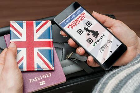 Uk vaccination passport concept: woman check the uk vaccination passport on her smartphone