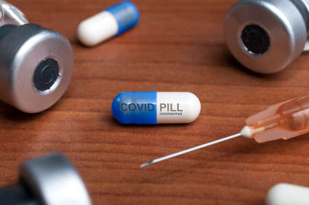 Covid pill to treat covid-19 coronavirus on a wooden table sorrounded by some vials and a syringe 스톡 콘텐츠