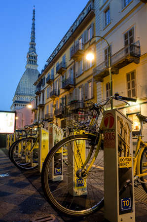 pollution free: TURIN, ITALY - SEPTEMBER 25, 2016 - Bike sharing station near the Mole Antonelliana, monument symbol of Turin in Italy, on september 25, 2016.
