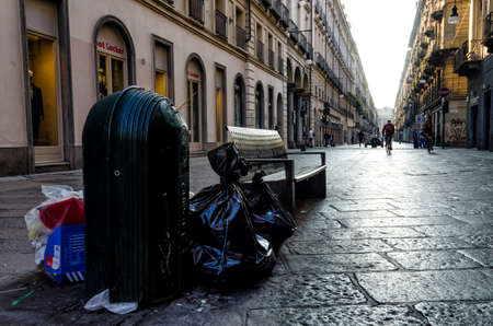 garibaldi: TURIN, ITALY - SEPTEMBER 25, 2016 - Via Garibaldi, main shopping street in the center of Turin (Italy), with trash can full and abandoned garbage on september 25, 2016