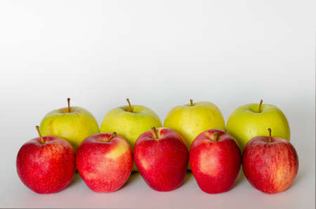 red and yellow apple in line with white background