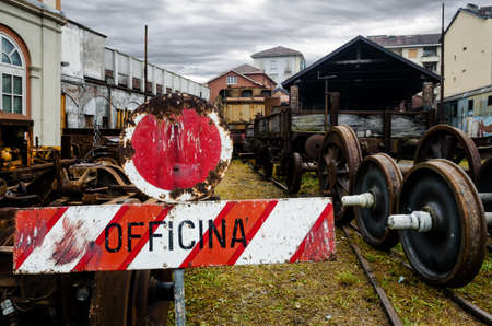 Rusty railcars in the old station of Turin Ponte Mosca (Italy), with signboard officina (meaning repair workshop) Stock Photo