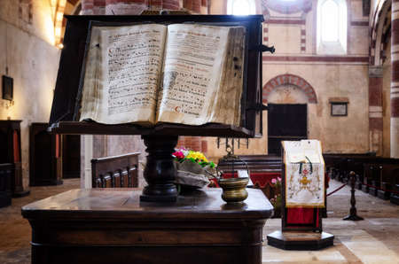 saluzzo: Ancient latin manuscript with religious chants and music sheets over a bookstand in the central nave of a romanesque church in an italian medieval abbey Editorial