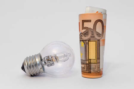 fifty euro money with an halogen light bulb and a white background Stock Photo