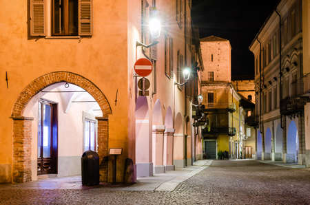 Piazza Risorgimento and the medieval colonnade of via Cavour, one of the main street of the town center of Alba (Piedmont, Italy) at night Stock Photo