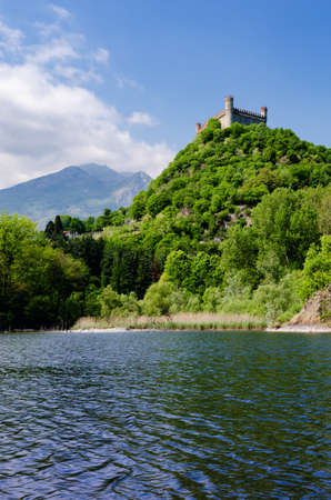 Castle of Montaldo Dora, in Canavese (Piedmont, Italy) with lake Pistono and Alps on the background Stock Photo