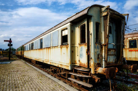 rusty car: Rusty old railcars and trains on an abandoned rail platform