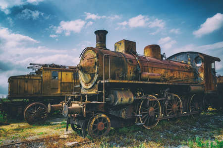 talian: Vintage looking photo of two rusty old talian steam and electric locomotives Stock Photo