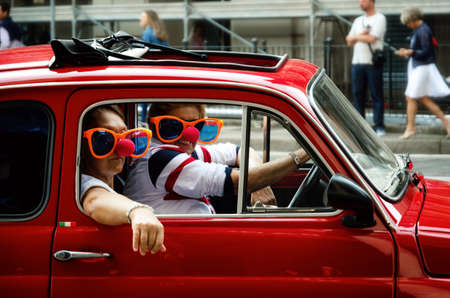 TURIN, ITALY - SEPTEMBER 24, 2017 - Funny looking couple driving an old red Fiat 500 during a classic car rally in Turin (Italy) on september 24, 2017 Editorial