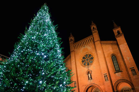 Piazza Risorgimento, main square of Alba (Piedmont, Italy) at night with the facade of Saint Lawrence cathedral and an illuminated christmas tree Stock Photo