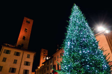 Piazza Risorgimento, main square of Alba (Piedmont, Italy) at night with the town hall, the medieval towers and an illuminated christmas tree