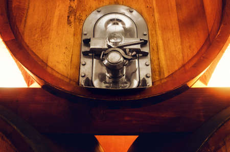 Old historic wine cellar in Langhe (Piedmont, Italy). Detail of a stainless steel valve on an oaken wine cask