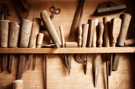Vintage colored image of carpenter tools hanging from the wall of a dusty workshop 스톡 콘텐츠