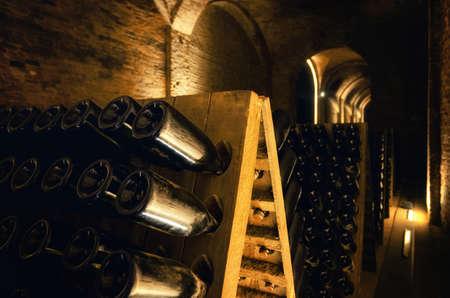 Pupitre y botellas dentro de una bodega subterránea para la producción de vinos espumosos de método tradicional en italia
