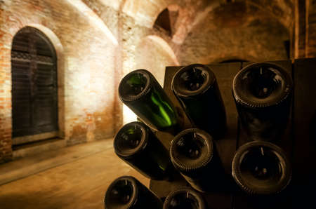Pupitre and bottles inside an underground cellar for the production of traditional method sparkling wines in italy Standard-Bild