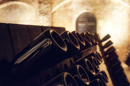 Pupitre and bottles inside an underground cellar for the production of traditional method sparkling wines in italy Stock Photo