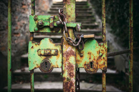 exterior view of a really old, closed and rusty green iron gate with chain and padlock Imagens