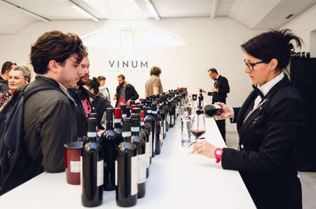 ALBA, ITALY - APRIL 25, 2019 – Female sommelier and man tasting traditional red nebbiolo wines of Piedmont at Vinum, wine e food show event of Alba, (Italy) on april 25, 2019 Editorial