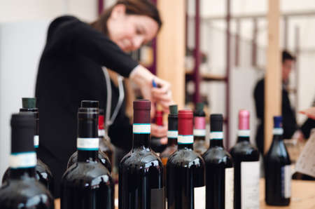 Tasting experience with bottles and an out of focus female sommelier uncorking a bottle of red dolcetto wine in the background