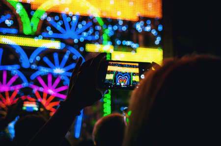 Light and music performance recorded with a smartphone held by a woman's hand during Cuneo Illuminata (Illuminated Cuneo), traditional public fair in Cuneo (Piedmont, Italy) Фото со стока