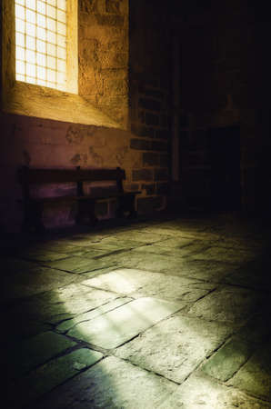Bright yellow light from an ancient medieval window illuminates the stone floor of a romanesque monastery church